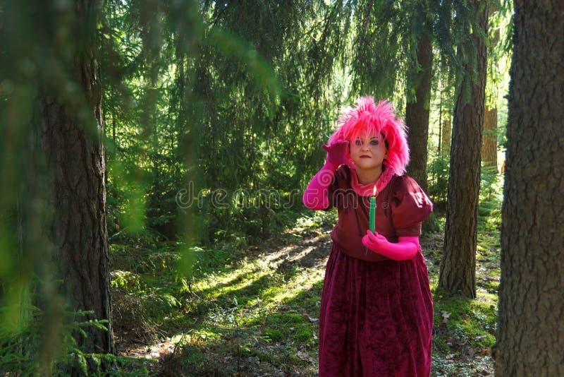 La bruja del bosque en ropa p?rpura conjura entre el bosque con las velas imagen de archivo