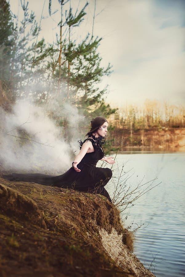 La bruja hermosa de la muchacha conjura en el bosque fotografía de archivo