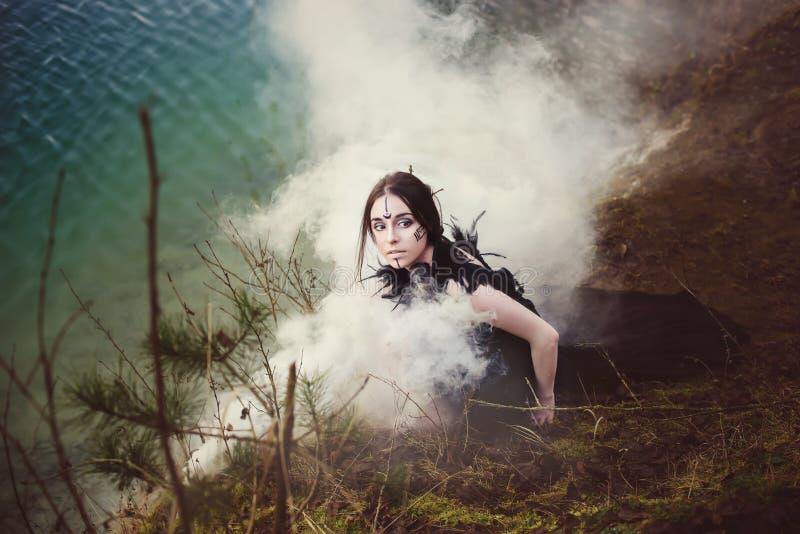 La bruja hermosa de la muchacha conjura en el bosque foto de archivo