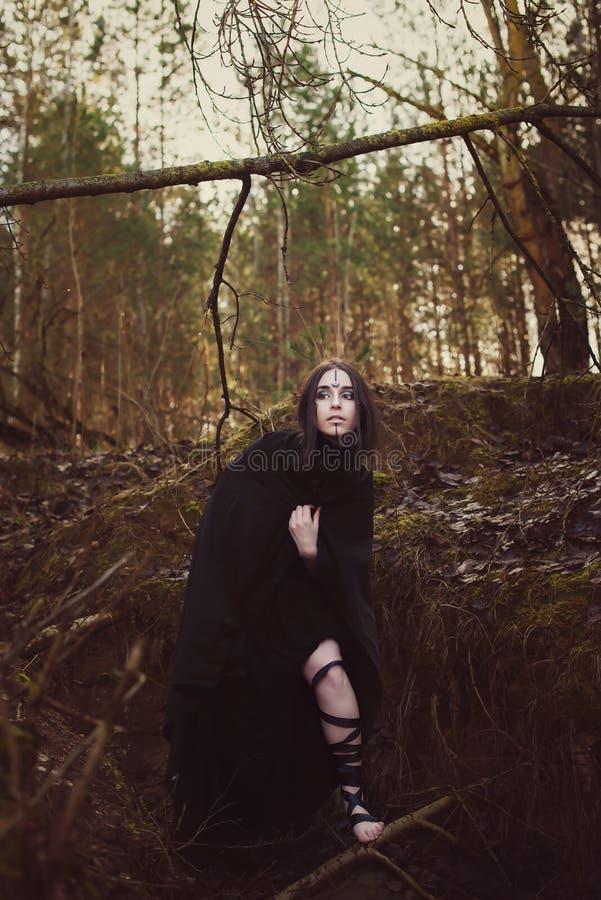 La bruja hermosa de la muchacha conjura en el bosque fotos de archivo