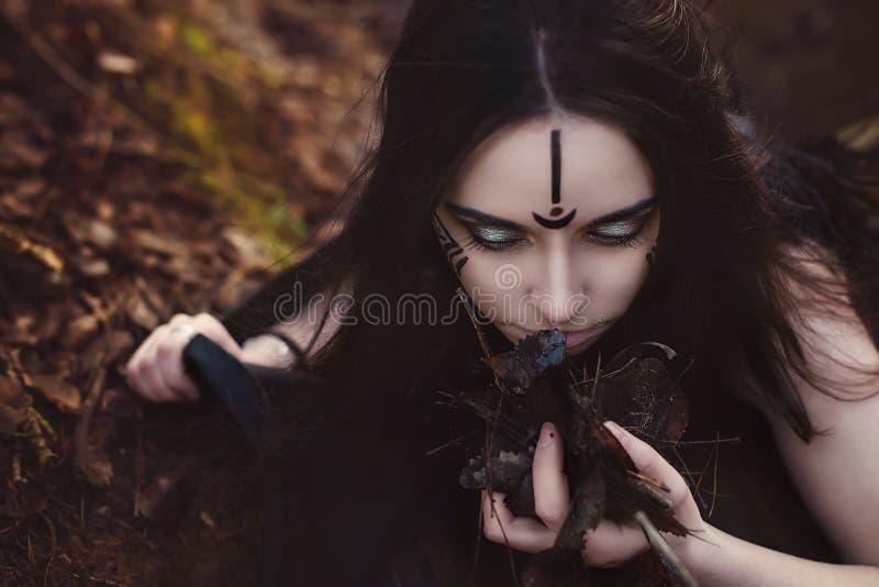 La bruja hermosa de la muchacha conjura en el bosque foto de archivo libre de regalías