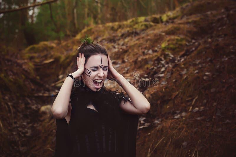 La bruja hermosa de la muchacha conjura en el bosque imagen de archivo