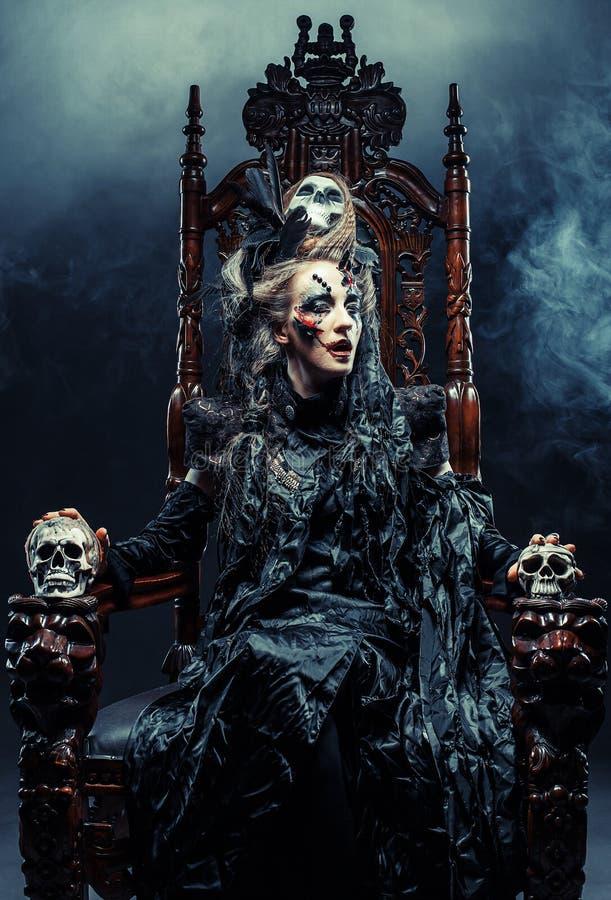 La bruja hermosa joven se sienta en una silla Brillante componga, cráneo, tema de Halloween del humo fotos de archivo