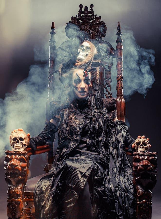 La bruja hermosa joven se sienta en una silla Brillante componga, cráneo, tema de Halloween del humo fotografía de archivo