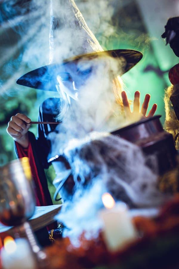La bruja joven está cocinando con magia fotografía de archivo