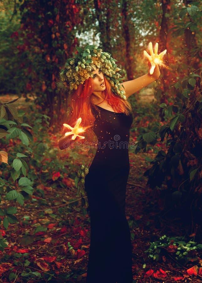 La bruja joven fantástica conjura en el bosque imagenes de archivo