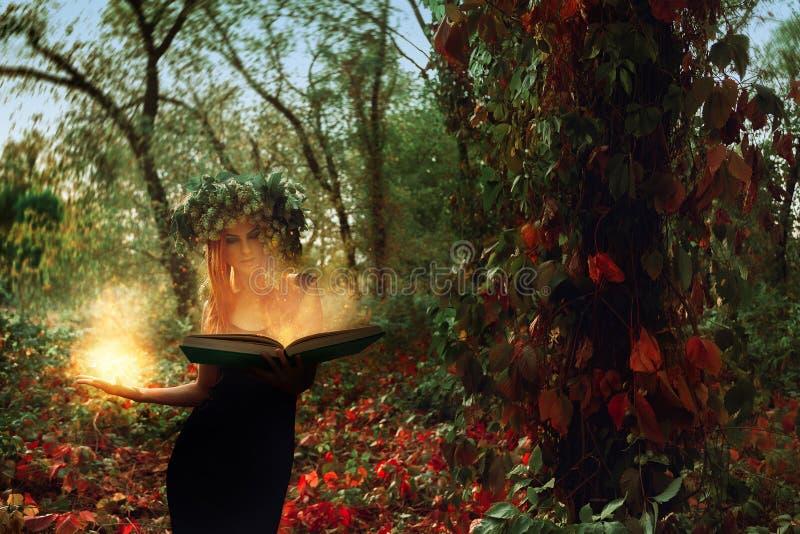 La bruja joven fantástica conjura por un libro mágico en el bosque fotos de archivo