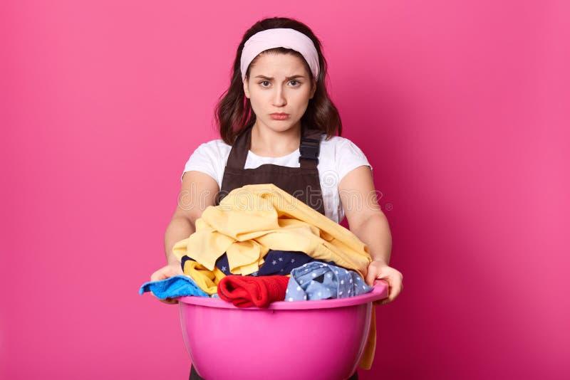 La bruna fastidioso esamina la tela sporca in bacino La giovane casalinga fa lavanderia Asciugamano crema sporco di colerd Ragazz fotografia stock