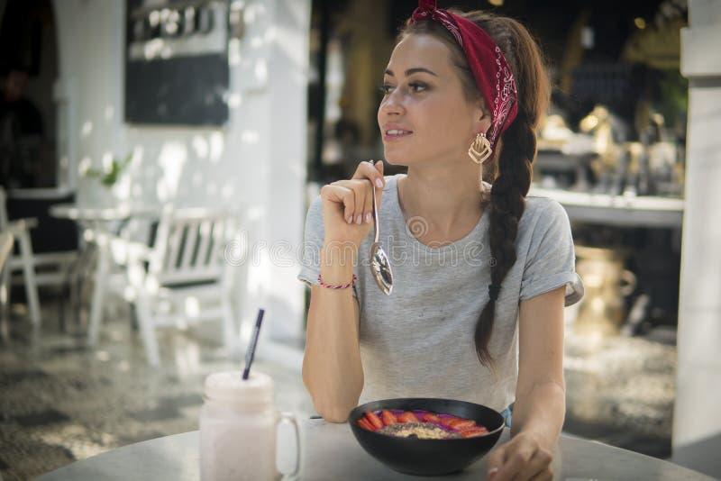 La brune avec une tresse prend le petit déjeuner en café de rue, photos stock