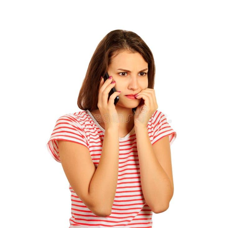 La brune dans un T-shirt rayé rouge parle du smartphone et les regards se sont inquiétés de la mauvaise nouvelle fille émotive d' photographie stock libre de droits