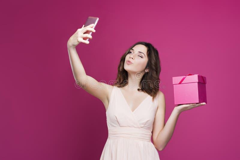 La brune dans une robe fait le selfie et tient un boîte-cadeau photo stock