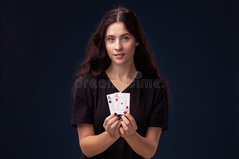 La brune de cheveux boucl?s pose avec des cartes de jeu dans des ses mains Concept de tisonnier sur un fond noir casino photo stock