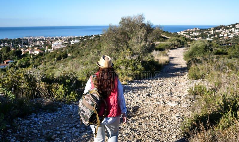 La brune de touristes dans un chapeau et un sac à dos va le long du chemin sur une colline à la ville par la mer photos stock