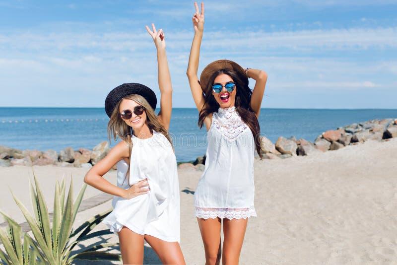 La brune deux attrayante et les filles blondes avec de longs cheveux se reposent sur la plage pr?s de la mer Ils utilisent des ch photographie stock libre de droits