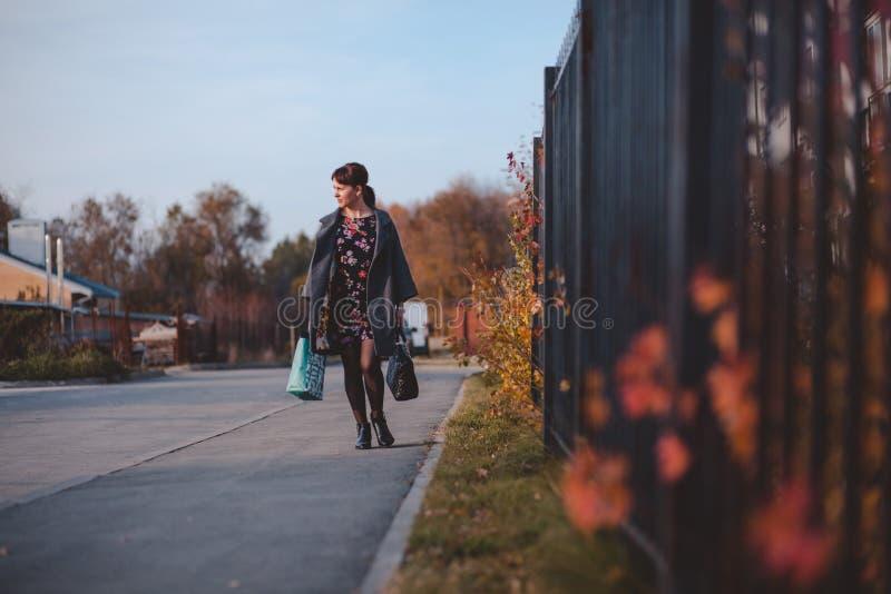 La brune heureuse dans un manteau de robe et va faire des emplettes en bas de la rue image libre de droits