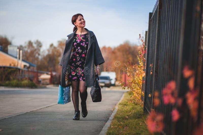 La brune heureuse dans un manteau de robe et va faire des emplettes en bas de la rue photos libres de droits