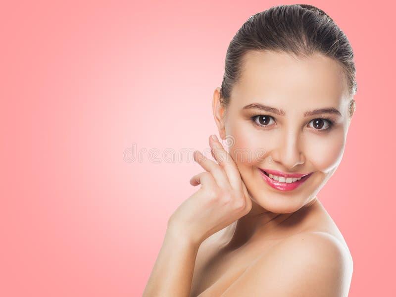 La brune modèle de belle fille avec sensible composent sur un fond rose avec un sourire regardant le bonheur d'émotions de caméra image libre de droits