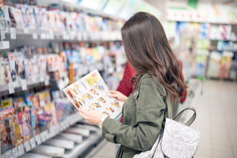 La brune se tient dans le mail près des étagères de magazine et regarde le catalogue produit photos libres de droits