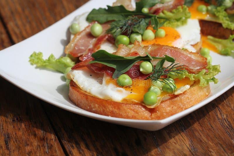 La Bruschetta con il rucola, il bacon chrispy, il pisello e l'uovo affogato è servito sul piatto bianco fotografie stock