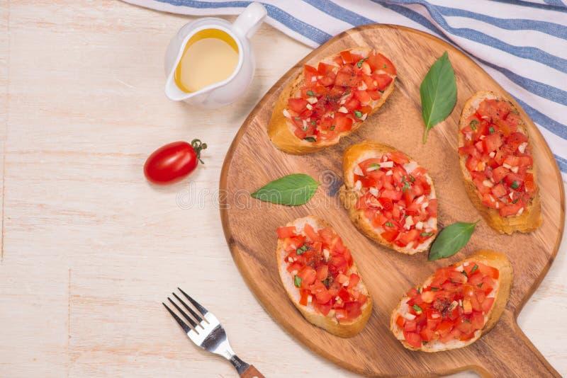 La Bruschetta italiana saporita con pane ha completato con il pomodoro e le erbe sul bordo di legno fotografia stock libera da diritti