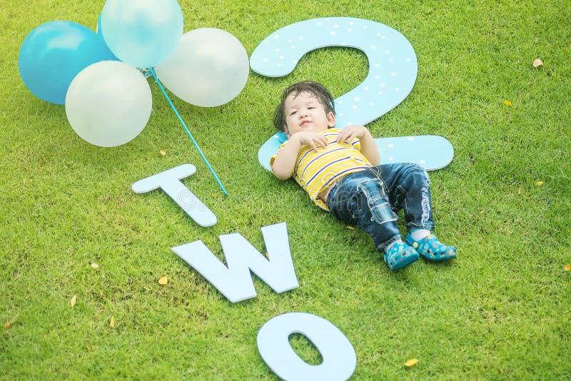 La bugia asiatica felice del bambino del primo piano sul pavimento dell'erba in parco ha strutturato il fondo nel secondo concett fotografie stock libere da diritti