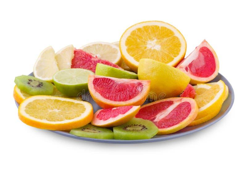 La bugia di frutti tropicali in un piatto su un bianco ha isolato il fondo Vista laterale immagini stock libere da diritti