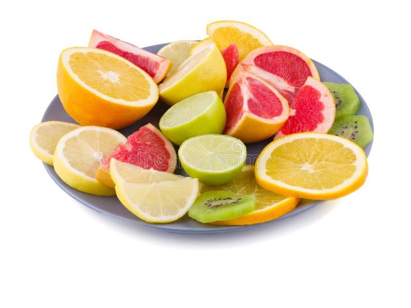 La bugia di frutti tropicali in un primo piano del piatto su un bianco ha isolato il fondo Vista laterale fotografia stock