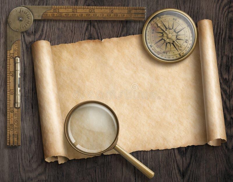 La bussola nautica d'annata e la lente di ingrandimento sulla tavola con il tesoro tracciano il rotolo fotografia stock libera da diritti