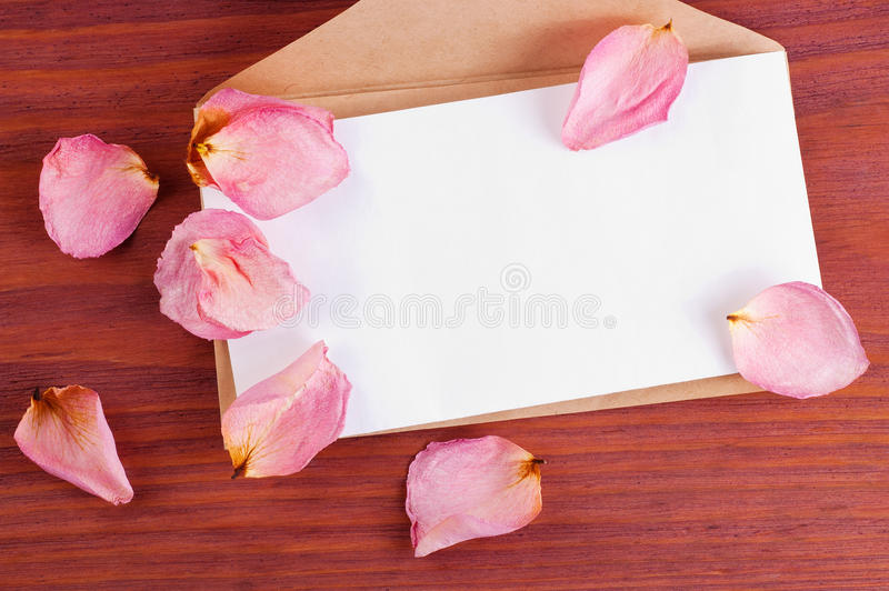 La busta della carta di Brown con lo strato bianco in bianco decorato ha sparso i petali rosa sulla tavola di legno con spazio pe fotografie stock libere da diritti
