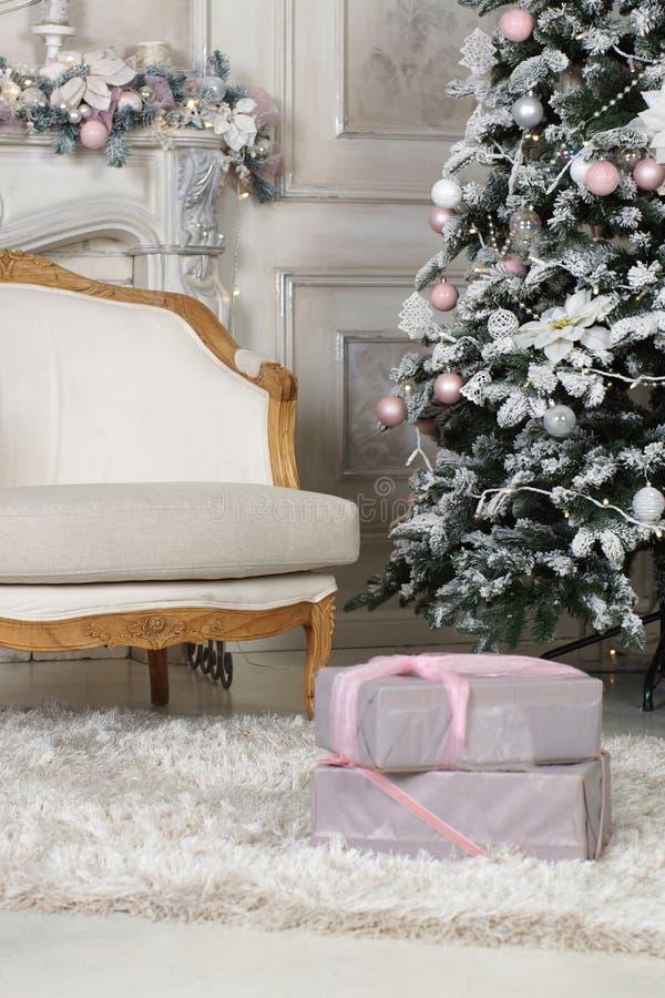 La butaca está en la sala de estar, adornada para la Navidad con un árbol y las guirnaldas fotografía de archivo
