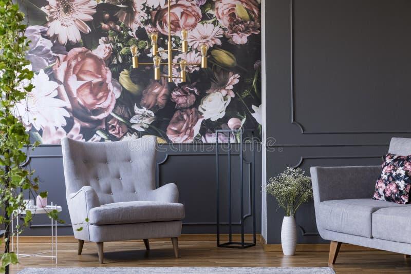 La butaca gris contra las flores wallpaper en inte oscuro de la sala de estar fotografía de archivo libre de regalías