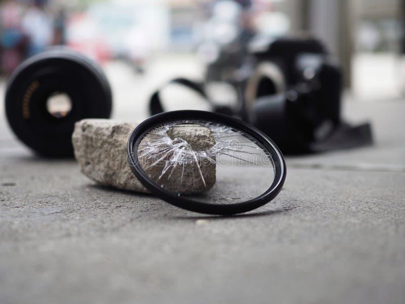 La cámara caída a la tierra, haciendo el filtro romperse, el len y el cuerpo dañados En el concepto del seguro de accidente encen foto de archivo libre de regalías