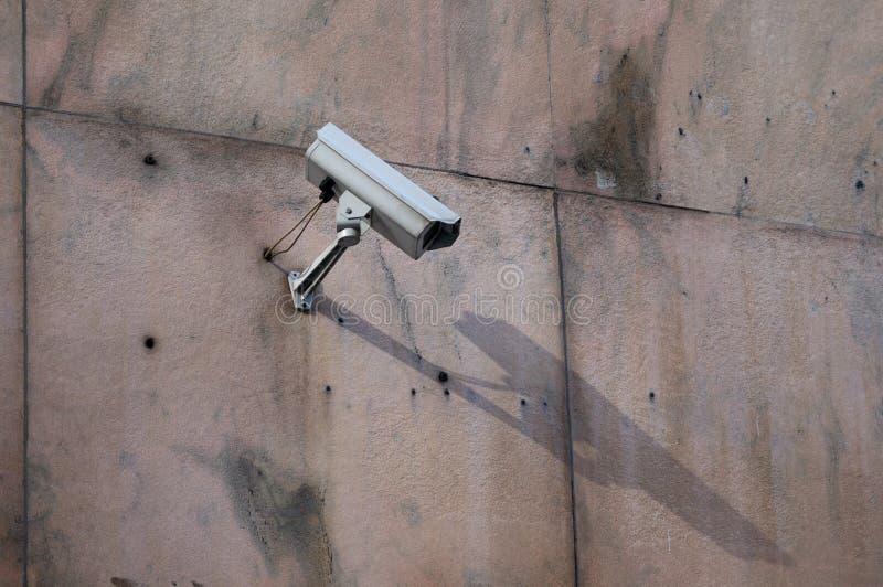 La cámara de seguridad en una pared resistida sucia está mirando siempre foto de archivo libre de regalías