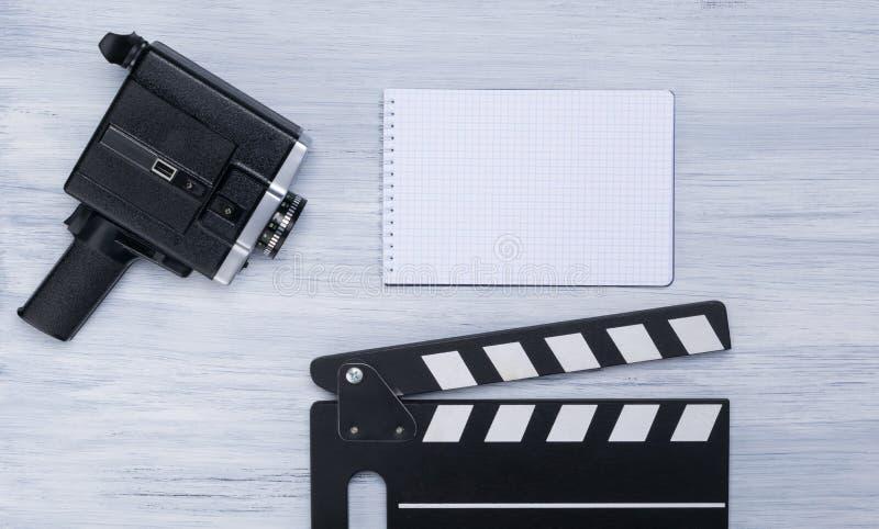 La cámara de vídeo vieja, dobla para el tiroteo y un cuaderno con un lugar para escribir en un fondo gris claro imágenes de archivo libres de regalías