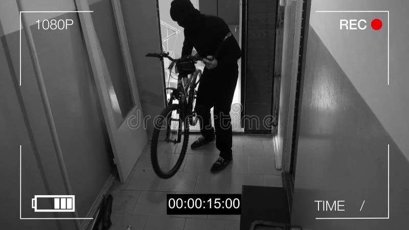 La cámara de vigilancia cogió al ladrón rompió la puerta y robó la bici foto de archivo