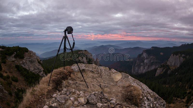 La cámara en un trípode está capturando la salida del sol en un soporte hermoso fotos de archivo