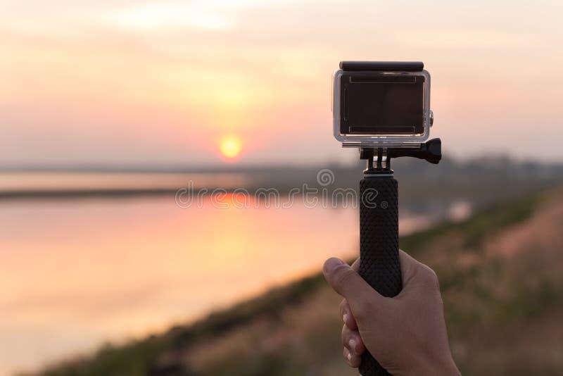 La cámara extrema del control de la mano toma la foto durante puesta del sol imagen de archivo libre de regalías