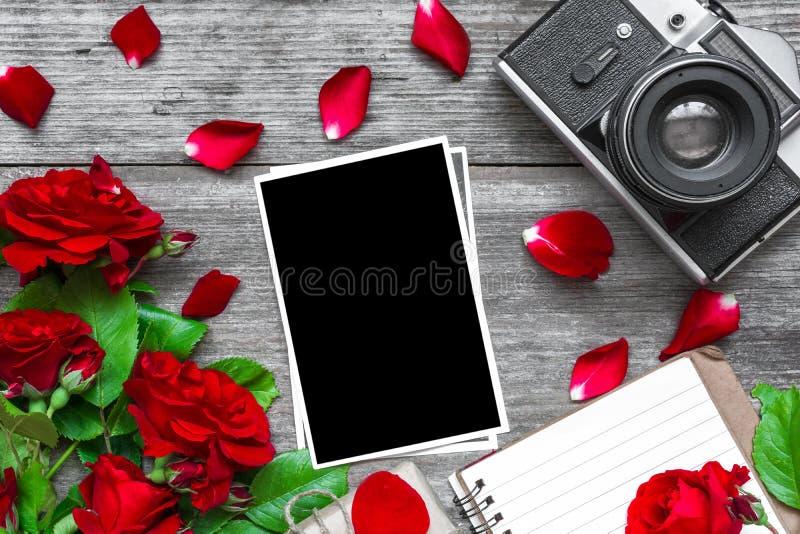 La cámara retra del vintage y el marco en blanco de la foto con la rosa del rojo florece el ramo y el cuaderno alineado imagen de archivo