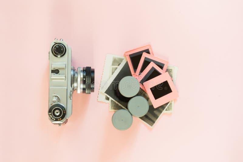 La cámara retra vieja con la caja tres para la foto de la película resbala en fondo rosado imagen de archivo