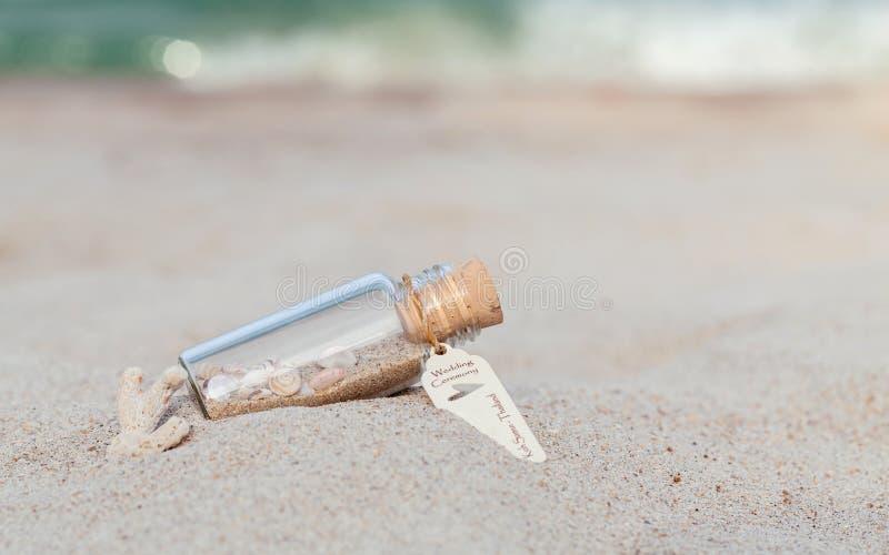 La cáscara de la arena y del mar en botella puso la playa fotos de archivo libres de regalías