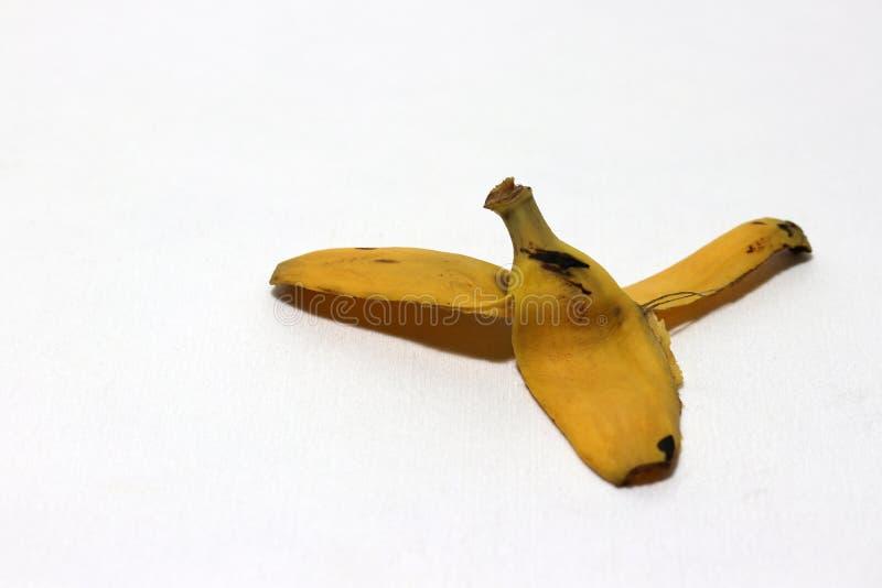 La cáscara del plátano fue dejada en el piso blanco El peligro puede deslizarse foto de archivo libre de regalías
