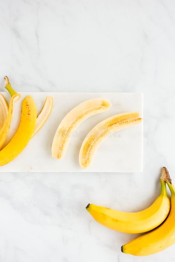 La cáscara del plátano y el plátano cortaron por la mitad en el mármol blanco fotografía de archivo