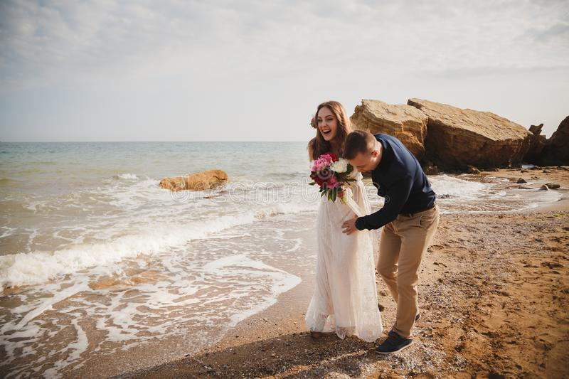 La cérémonie de mariage extérieure de plage près de la mer, le marié de sourire heureux élégant et la jeune mariée ont l'amusemen photo stock