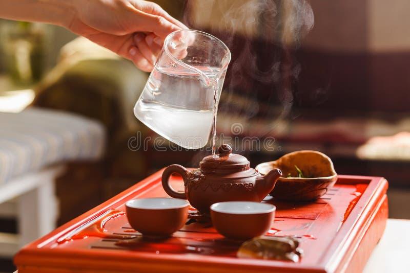 La cérémonie de thé La femme rince la théière photographie stock libre de droits