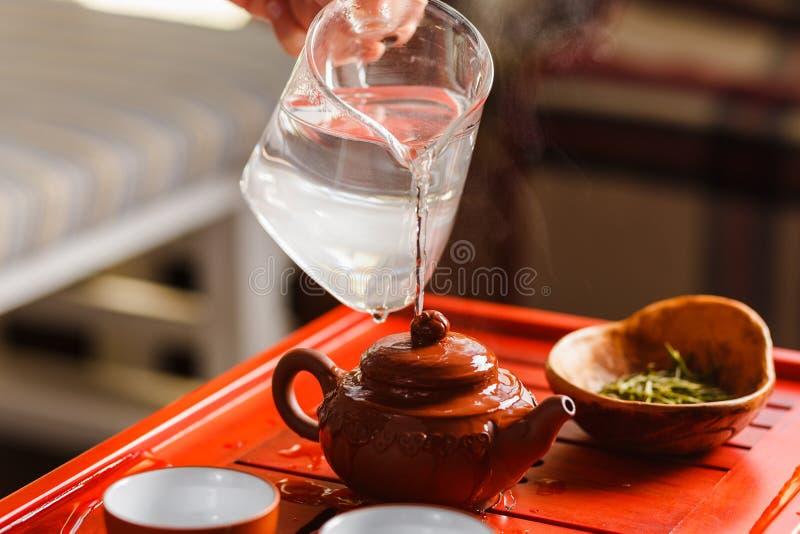 La cérémonie de thé La femme rince la théière images libres de droits