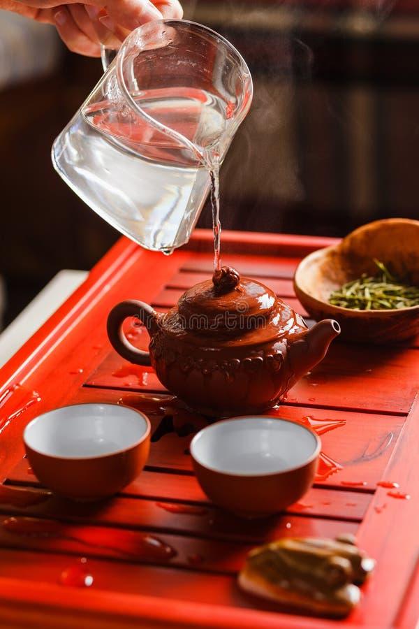 La cérémonie de thé La femme rince la théière photo stock