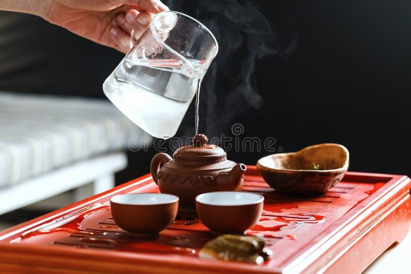 La cérémonie de thé La femme rince la théière image libre de droits