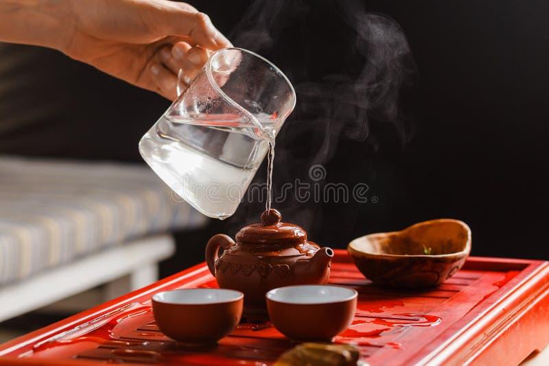 La cérémonie de thé La femme rince la théière photos libres de droits