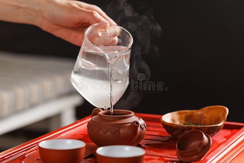 La cérémonie de thé La femme verse l'eau chaude dans la théière photographie stock libre de droits