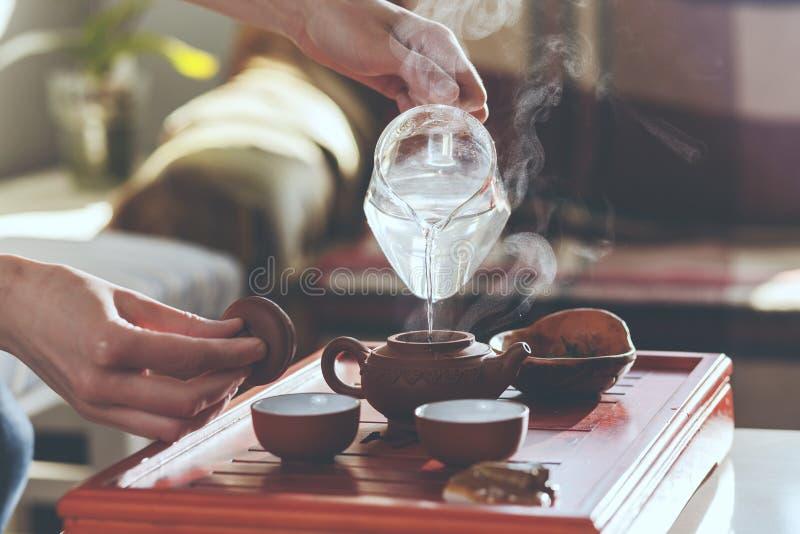 La cérémonie de thé La femme verse l'eau chaude dans la théière photographie stock